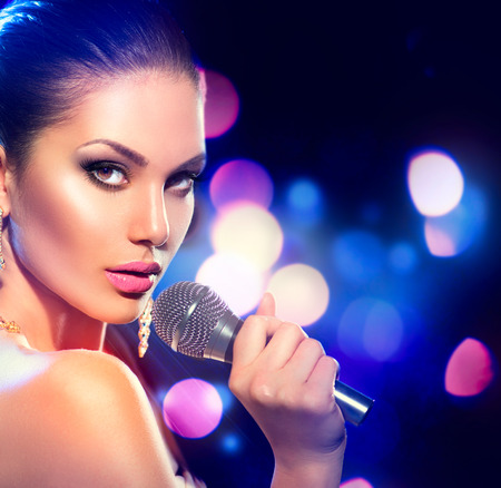 karaoke: Woman with microphone over blinking bokeh night background