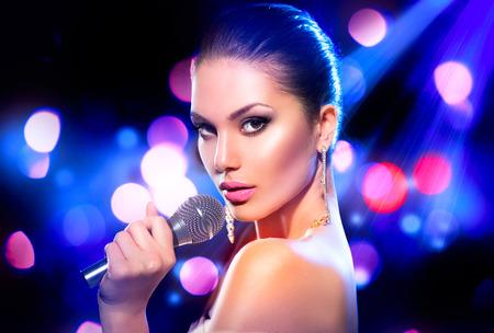 cantando: Mujer con el micrófono sobre el parpadeo bokeh fondo de la noche