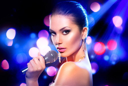 Woman with microphone over blinking bokeh night background