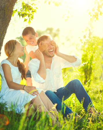 family on grass: Happy joyful young family having fun outdoors Stock Photo