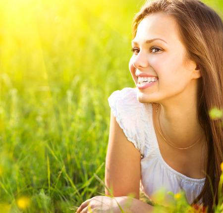 Beauty romantic girl lying on summer field