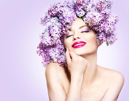 Chica modelo de manera de la belleza con flores lilas peinado