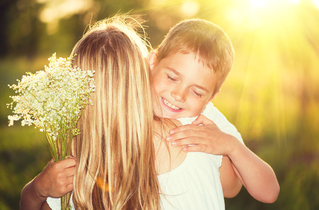 two girls hugging: Mother and her little son with bouquet of flowers outdoors