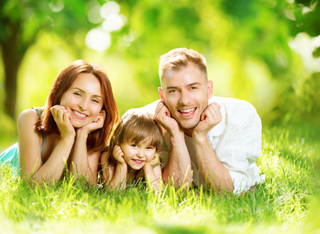 家族: 夏の公園で楽しんで幸せなうれしそうな若い家族