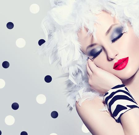 Bellezza modella ragazza con piume bianche acconciatura