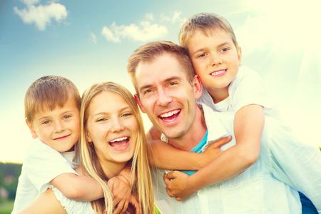 familias felices: Feliz alegre joven familia se divierten en el parque de verano