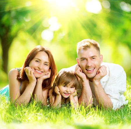 familias unidas: Feliz alegre joven familia se divierten en el parque de verano
