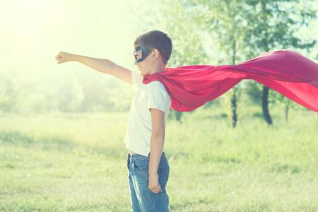 Weinig jongen die superheld kostuum outdoor