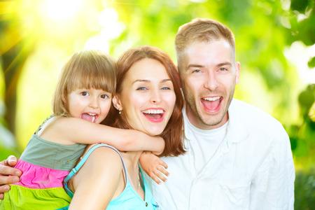 niños riendose: Familia feliz joven alegre al aire libre