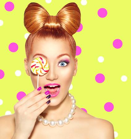 golosinas: Modelo de moda Muchacha de la belleza que come el lollipop colorido Foto de archivo