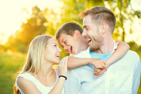 Happy joyful young family having fun outdoors Foto de archivo