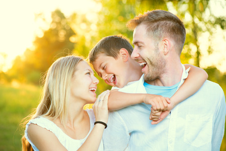 Happy joyful young family having fun outdoors Banco de Imagens