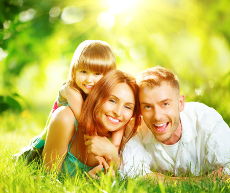 Happy joyful young family playing together in summer park Stock Photo