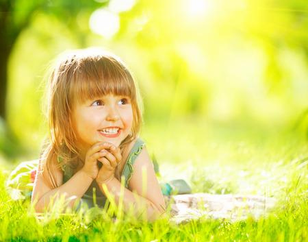 dia soleado: Retrato de una niña sonriente acostado en la hierba verde Foto de archivo