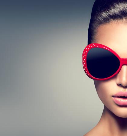 jovem: Menina da beleza do modelo de forma morena usando óculos de sol à moda Imagens
