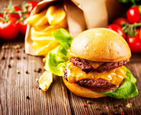 Double cheesburger with fries on wooden table photo