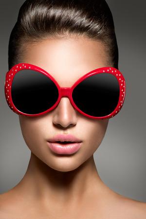 moda: Muchacha de la belleza del modelo de manera morena que llevaba gafas de sol elegantes
