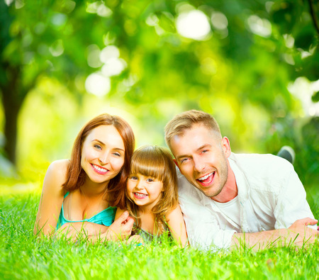 Happy joyful young family lying on green grass