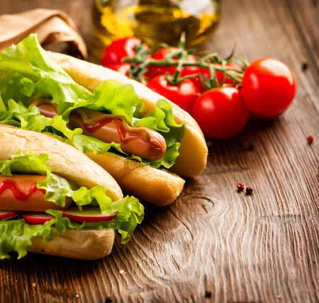 perro comiendo: A la parrilla perros calientes con mostaza y salsa de tomate en una mesa de madera de picnic