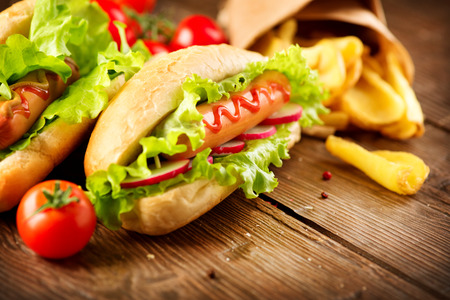 Grilled hot dogs with mustard and ketchup on a picnic wooden table