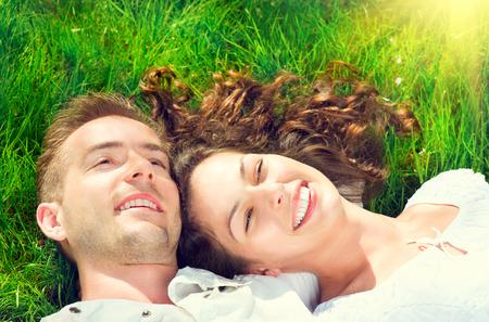 Os pares de sorriso felizes que relaxam na grama verde