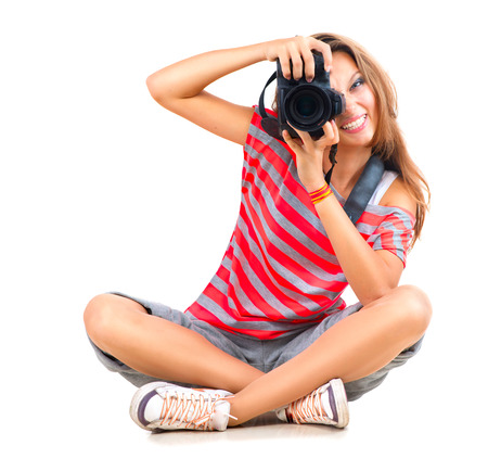 Beauty teenage girl photographer sitting over white background