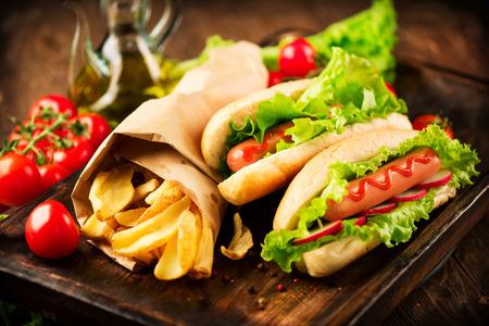 embutidos: A la parrilla perros calientes con mostaza y salsa de tomate en una mesa de madera de picnic