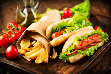 frankfurter: Grilled hot dogs with mustard and ketchup on a picnic wooden table