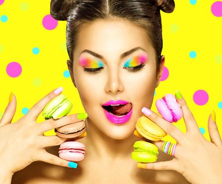 Người mẫu thời trang vẻ đẹp cô gái với gương trang điểm đầy màu sắc lấy bánh hạnh nhân đầy màu sắc
