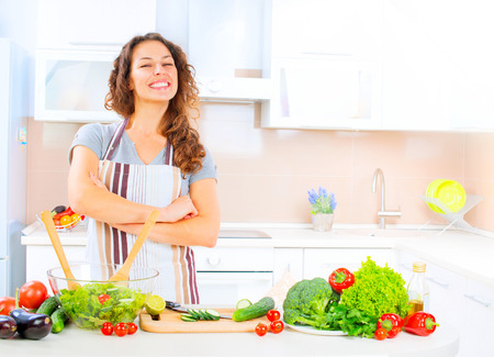 vegan food: Happy young woman cooking in the kitchen at home Stock Photo