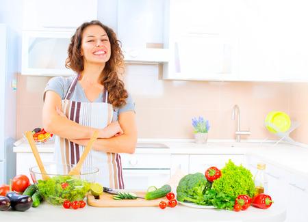 comer sano: Mujer joven feliz que cocina en la cocina en el hogar Foto de archivo