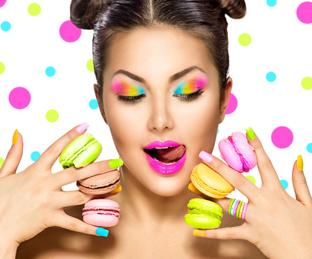 Beauty fashion model girl with colourful makeup taking colorful macaroons