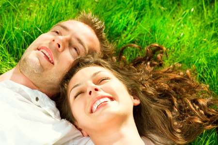 man lying down: Happy smiling couple relaxing on green grass