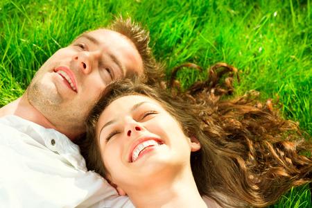 persona alegre: Sonriente pareja feliz que se relaja en la hierba verde