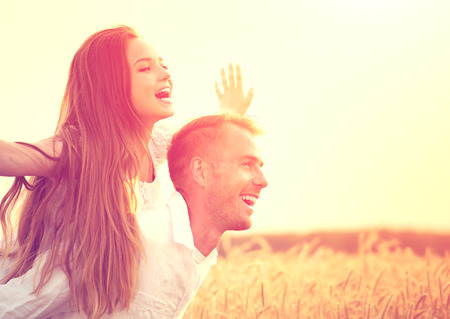 Happy couple having fun outdoors on wheat field over sunset Stockfoto