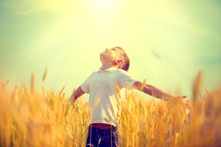 niño corriendo: Niño pequeño en un campo de trigo en la luz del sol disfrutando de la naturaleza Foto de archivo