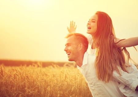 Casal feliz se divertindo ao ar livre no campo de trigo sobre o por do sol