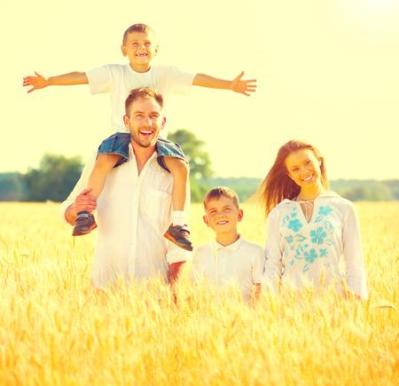 Glad ung familj med två barn går på vete sommar fält