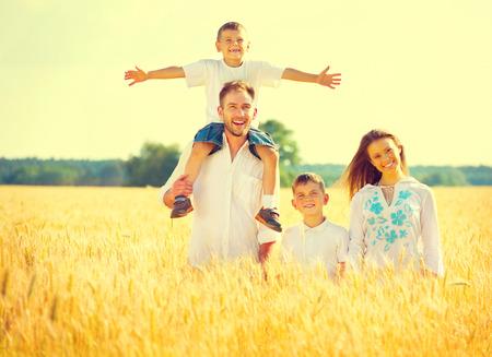 paisaje rural: Familia joven feliz en el campo de verano de trigo