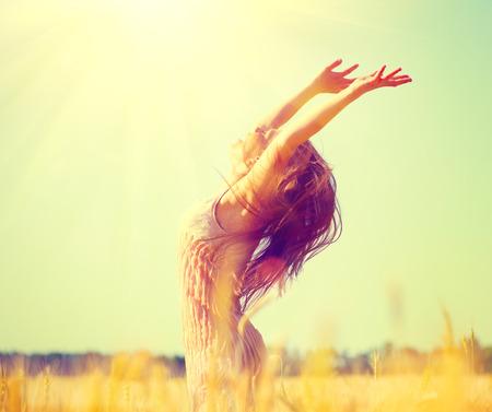 flare up: Beauty girl outdoors enjoying nature on wheat field