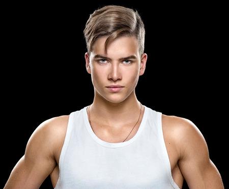 Knappe atletische jonge man die op een zwarte achtergrond