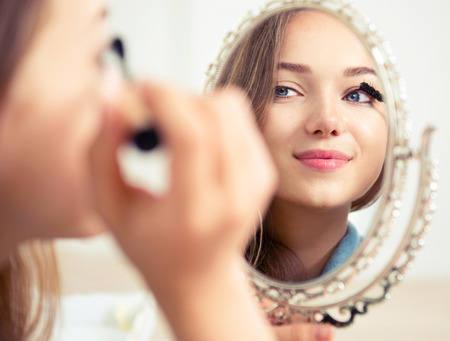 makeup a brush: Beauty model teenage girl looking in the mirror and applying mascara