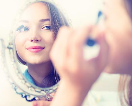 Güzellik modeli kız aynaya bakarak ve maskarayı uygulayarak