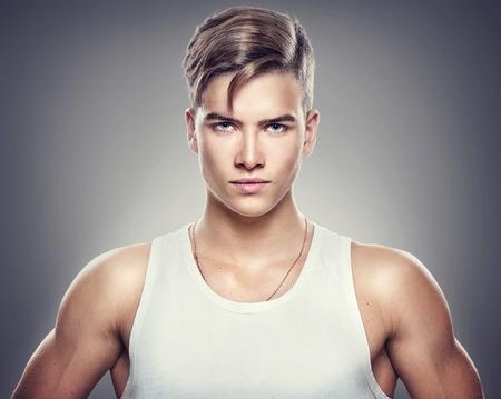 Knappe atletische jonge man die op een grijze achtergrond