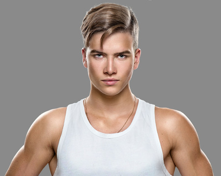 attraktiv: Stattlicher athletischer junger Mann auf grauem Hintergrund isoliert