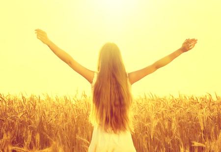 A menina da beleza ao ar livre que levanta as mãos em raias da luz solar