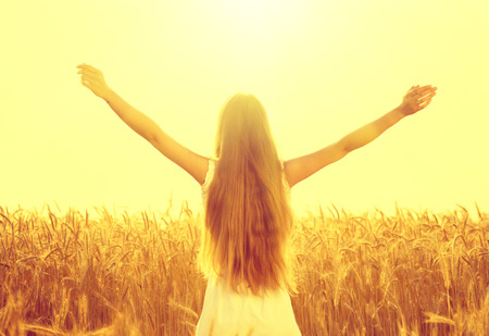 Beauty girl outdoors raising hands in sunlight rays Stock Photo