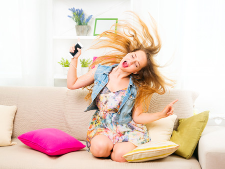 equipo de sonido: Pretty adolescente sentado en el sof� en casa con su tel�fono inteligente, escuchar m�sica Foto de archivo