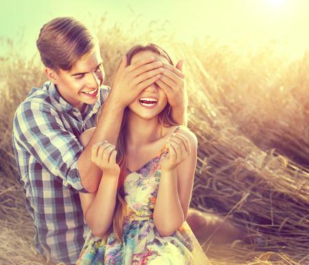 ragazza innamorata: Coppie felici che hanno divertimento all'aperto sul campo di grano, il concetto di amore