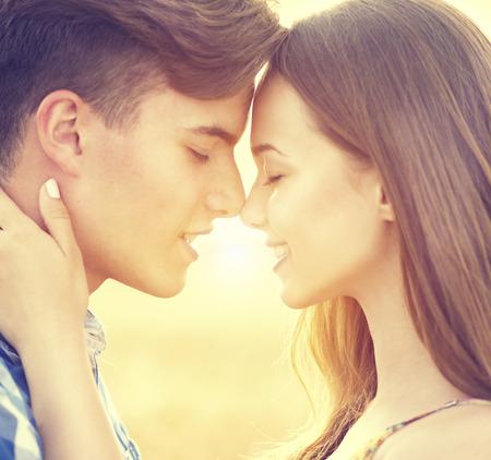 pareja besandose: Feliz pareja bes�ndose y abraz�ndose al aire libre en campo de trigo, el concepto de amor